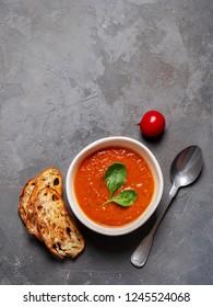 Tomato soup bowls on concrete background. Top view. Copy space.