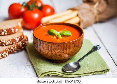 Tomato soup with bread sticks and basil on wooden background