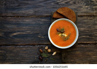 Tomato soup with cheese, olives and herbs. Dark wooden background