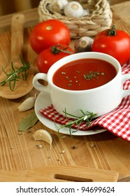 Tomato soup, fresh tomatoes, garlic and rosemary on wooden