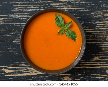 Tomato soup with fresh tomatoes, herbs and olive oil, basil on black stone background.