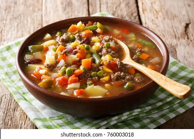 Tomato soup with ground beef and vegetables close-up in a bowl on the table. horizontal