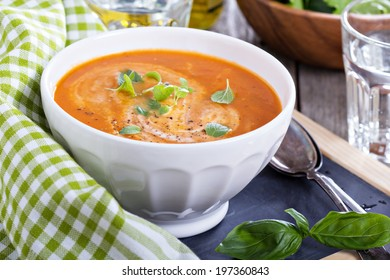 Tomato soup with herbs in white bowl