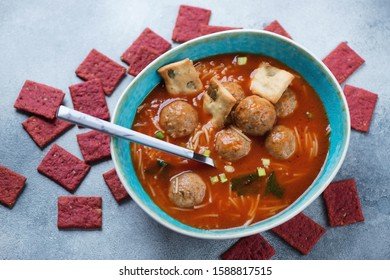 Tomato soup with meatballs and vermicelli in a turquoise bowl, elevated view over light-blue stone surface with crackers