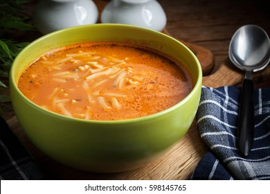 Tomato soup with noodles on a wooden table. Dark light.