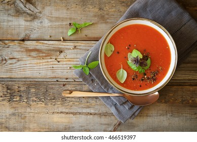 Tomato soup on wooden table, top view