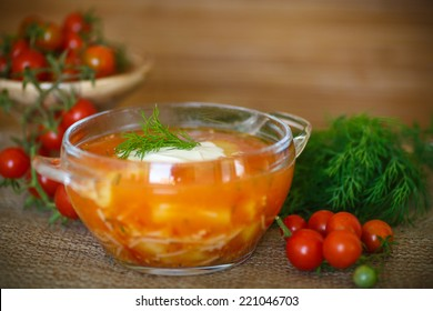 tomato soup with pasta in a bowl on a wooden table