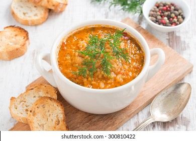 tomato soup with rice and vegetables in a white saucepan and bread, top view, horizontal