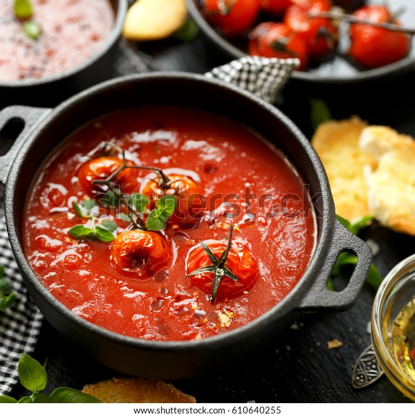 Tomato soup with roasted tomatoes, top view, black background