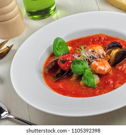 Tomato soup with sea food on a wooden table. Delicious Italian healthy food in a plate.