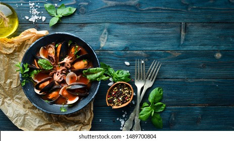 Tomato soup with seafood. Mussels, clams and octopuses. In the old background. Top view. Free copy space.