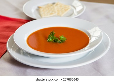 Tomato soup in a white bowl with garnish and crackers in the background