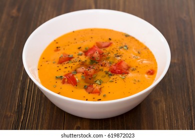 tomato soup in white bowl on wooden background