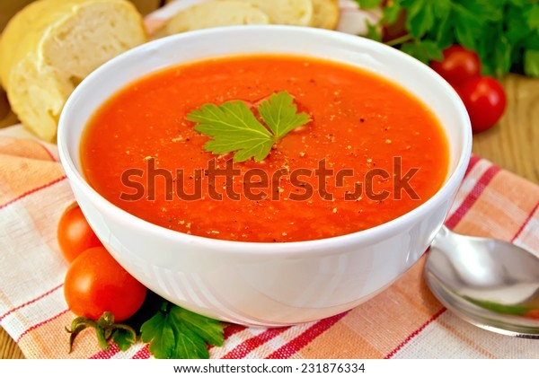 Tomato soup in a white bowl on a napkin, spoon, tomatoes, parsley, bread on a wooden boards background