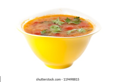 tomato soup in a yellow bowl on a white background
