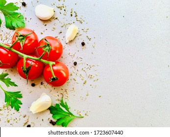 Tomato, spices, pepper, garlic, parsley, herb. Vegan diet food, creative cherry tomato composition isolated on gray background. Organic fresh vegetables. Copyspace, top view.