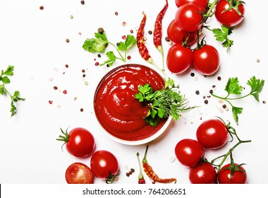 Tomato spicy ketchup sauce with cherry tomatoes in a bowl on white food background, top view