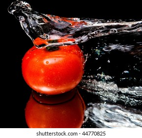 Tomato and splash water over black background