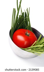 tomato and spring onion inside metal bowl on white