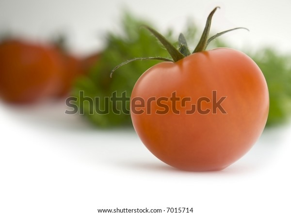 Tomato: Straight Product Shot taken in Studio in Natural Light with other Tomatoes and Herbs in Background