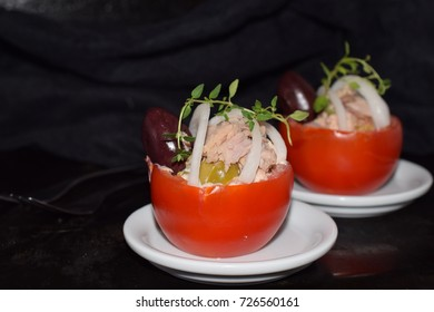 Tomato stuffed with tuna olives and onions.