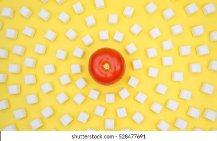Tomato surrounded by a sugar-cubes