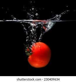 Tomato thrown into water on black background.