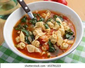 Tomato tortellini spinach soup on a rustic table