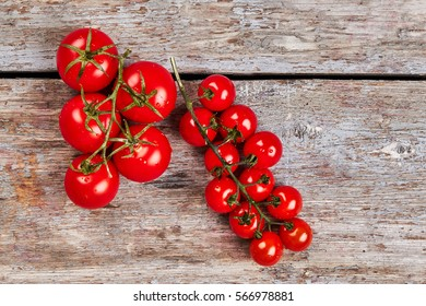 Tomato twig on wooden background. Red cherry tomatoes. Healthy fresh food.