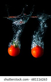Tomato under water. Cherry the tomato in the water. Splash of water.