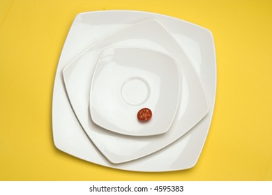 Tomato in white plate over yellow