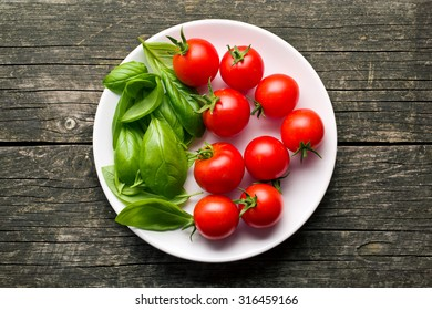 tomatoes and basil leaves on plate