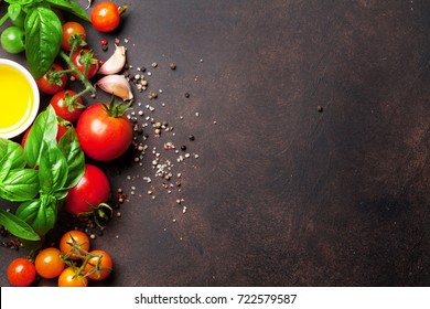 Tomatoes, basil and spices on stone table. Cooking concept. Top view with space for your text