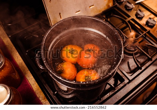 Tomatoes being boiled for the peeling process of canning.