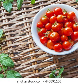 Tomatoes in bowl, ripe and red harvest, on wicker picnic basket, with tomato leaves - with text / copy space - square composition.