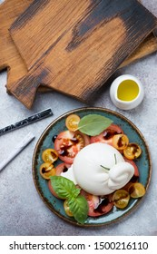 Tomatoes and burrata cheese salad, flatlay on a beige stone background with wooden chopping boards, studio shot