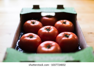 Tomatoes in cardboard box on a wooden table