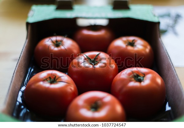 Tomatoes in a cardboard box on a wooden table