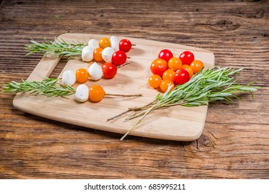 Tomatoes and cheese balls on rosemary skewers