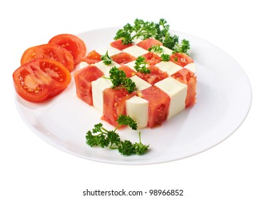 tomatoes and cheese composed in checkerboard pattern on plate