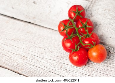 Tomatoes cherry branch on rustic wooden white table