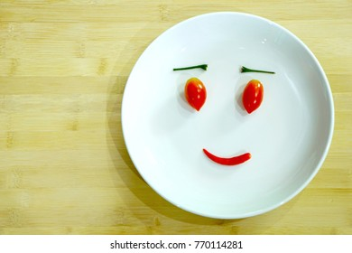 Tomatoes and chili pepper making happy face on white plate. Two tomatoes for eyes and spicy pepper for mouth. Smiley  emotion made from vegetables. Food art concept. Love vegetable.
