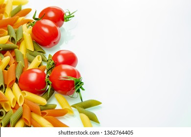 Tomatoes and colored pasta, on the left side of the frame.