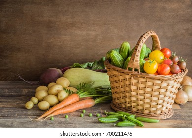 Tomatoes and cucumbers in the basket. Different vegetables on the wooden table. Food background.