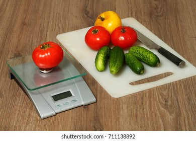 Tomatoes, cucumbers and knife on a cutting Board. Tomato on the kitchen scales.