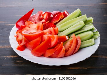 tomatoes, cucumbers and pepper on a wooden surface. healthy diet food. on dark background fresh vegetables are sliced ??on a plate.