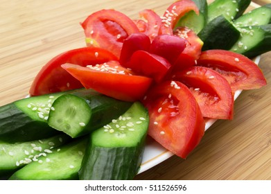 Tomatoes and cucumbers sliced and sprinkled with sesame seeds on wooden background