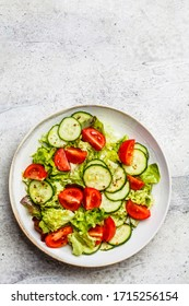 Tomatoes and cucumbers vitamin salad in a white bowl, gray background. Healthy food concept.
