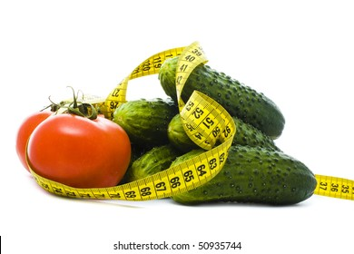 tomatoes and cucumbers with yellow measuring tape isolated on white