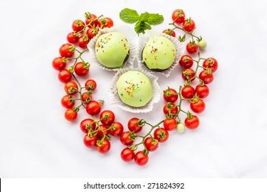 Tomatoes. Fresh cherry tomatoes wiht chocolate ball on white background